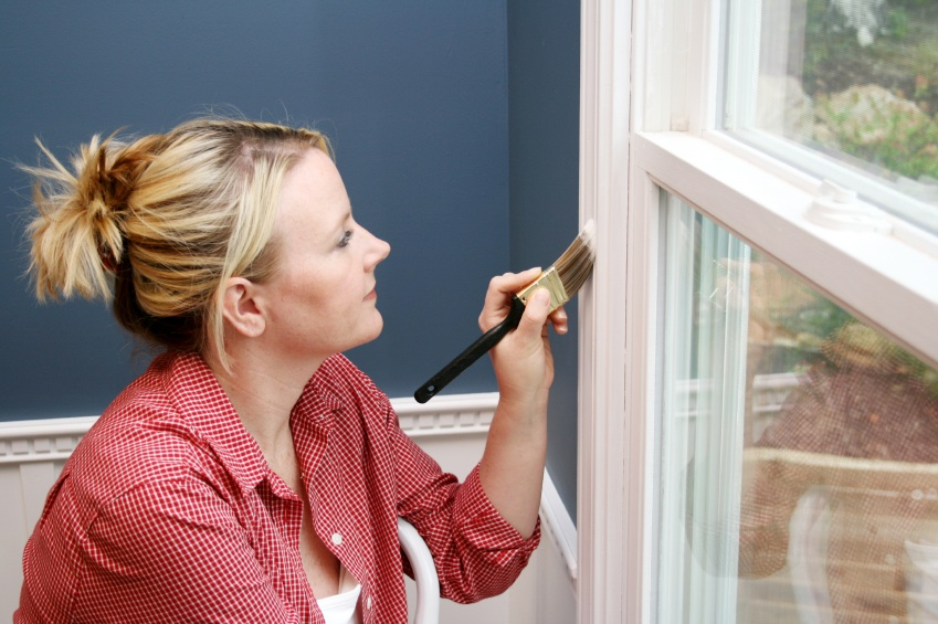 Woman paints window trim in her home